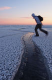 Hiker jumping over a crack in ice Stock Images