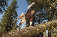 Hiker Jumping Over Fallen Tree In Forest Stock Photos