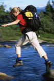 Hiker jumping from rock to rock Royalty Free Stock Photos
