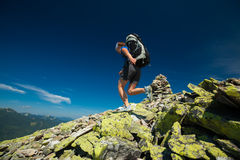Hiker jumps over stones Royalty Free Stock Image