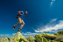 Hiker jumps over stones Stock Images