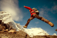 Hiker jumps on the rock Stock Images