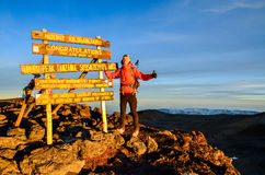 Hiker at Kilimanjaro summit - Tanzania, Africa. Kilimanjaro, Tanzania - March 11, 2015: A hiker standing on Uhuru Peak, the summit of Kibo and highest mountain Royalty Free Stock Photography