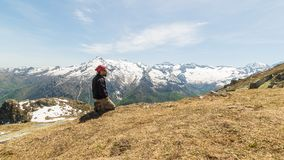 Hiker kneeling on the mountain top Royalty Free Stock Images