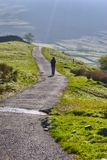 Hiker in Lake District. Rear view of female hiker walking on pathway in Lake District National Park, Cumbria, England Royalty Free Stock Photos
