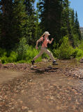 Hiker leaping over stream. Female hiker leaping over stream Stock Photos