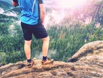 Hiker legs climbing on sunrise mountain peak rock. Slim legs stock photos