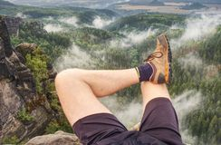 Hiker legs climbing on sunrise mountain peak rock. Slim legs stock image
