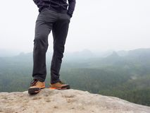 Hiker legs in comfortable trekking  boots on rock. Man legs in light outdoor trousers, leather shoes. Hiker legs in comfortable trekking  boots stand on rocky Stock Photos