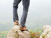 Hiker legs in comfortable trekking  boots on rock. Man legs in light outdoor trousers, leather shoes. Hiker legs in comfortable trekking  boots stand on rocky Stock Photography