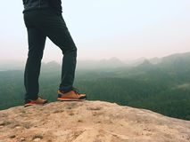 Hiker legs in comfortable trekking  boots on rock. Man legs in light outdoor trousers, leather shoes. Hiker legs in comfortable trekking  boots stand on rocky Royalty Free Stock Image