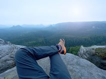 Hiker legs in comfortable trekking  boots on rock. Man legs in light outdoor trousers, leather shoes. Hiker legs in comfortable trekking  boots stand on rocky Stock Images