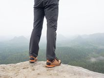 Hiker legs in comfortable trekking  boots on rock. Man legs in light outdoor trousers, leather shoes. Hiker legs in comfortable trekking  boots stand on rocky Royalty Free Stock Photography