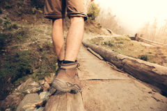 Hiker legs crossing the edge of mountain river bridge Stock Photos