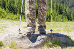 Hiker legs in hiking boots and part of trekking poles Stock Photography