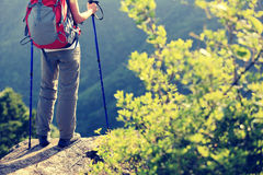 Hiker legs stand on mountain peak rock. Woman hiker legs stand on mountain peak rock Royalty Free Stock Images