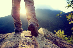 Hiker legs stand on mountain peak rock Royalty Free Stock Image