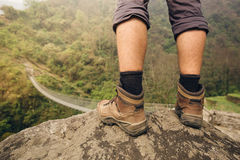 Hiker legs standing on rock above mountain suspension bridge Stock Image