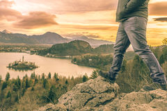 Hiker legs and view over Lake Bled. Man equipped with hiking shoes climbed on rocks above the lake Bled from Slovenia, in a December morning day Royalty Free Stock Image