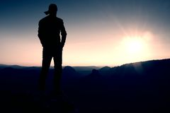 Hiker in long cap on rock empire and watching to Sun. Beautiful moment the miracle of nature Stock Photo