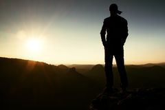 Hiker in long cap on rock empire and watching to Sun. Beautiful moment the miracle of nature Stock Photos