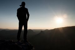 Hiker in long cap on rock empire and watching to Sun. Beautiful moment the miracle of nature Stock Images