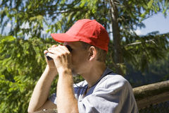 Hiker looking through binoculars Stock Photo