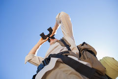 Hiker looking through binoculars on country trail Royalty Free Stock Photos