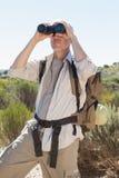 Hiker looking through binoculars on country trail Stock Image