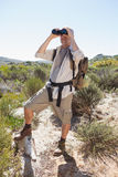 Hiker looking through binoculars on country trail Stock Photography