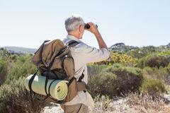 Hiker looking through binoculars on country trail Royalty Free Stock Images