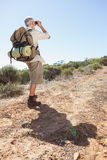 Hiker looking through binoculars on country trail Royalty Free Stock Photo