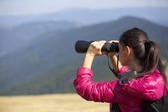 Hiker looking in binoculars enjoying spectacular view on mountai Stock Images