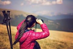 Hiker looking in binoculars enjoying spectacular view on mountai Royalty Free Stock Photo