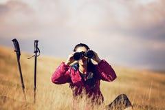 Hiker looking in binoculars enjoying spectacular view on mountai Royalty Free Stock Images