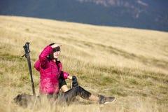 Hiker looking in binoculars enjoying spectacular view on mountai Stock Image