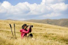 Hiker looking in binoculars enjoying spectacular view on mountai Stock Photography