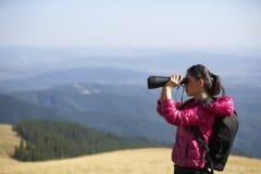 Hiker looking in binoculars enjoying spectacular view on mountai Stock Photo