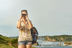Hiker looking in binoculars enjoying view coast during hiking tr royalty free stock image