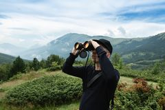Hiker looking through binoculars in front of hills and mountain royalty free stock photography