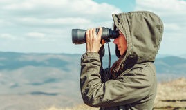 Hiker looking in binoculars in the mountains Stock Images