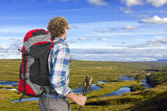 Hiker, looking into the distance. Hiker looking into the distance, upstream a small river, shielding his eyes and holding two walking sticks Royalty Free Stock Photo