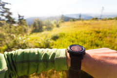 Hiker looking at electronic compass, travel and navigation Royalty Free Stock Images