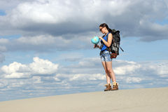 Hiker looking at a globe where they will travel Stock Images