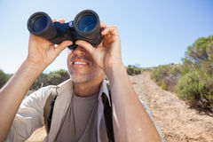 Hiker looking through his binoculars on country trail Stock Photos