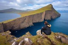 Hiker looking at the lake Sorvagsvatn on Faroe Islands