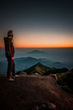 Hiker looking at mountains. Hiker stands at top of mountain and looks at Mount Merbabu, dormant stratovolcano, covered with morning fog during sunrise near Yogya Royalty Free Stock Images