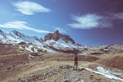 Hiker looking the outstanding view of high altitude landscape and majestic snowcapped mountain peak in autumn season. Wide angle s Royalty Free Stock Images
