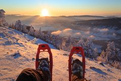 Snowshoe sunset. Hiker looking over his snowshoes at the snowcovered landscape in the mountains during sunset Royalty Free Stock Image