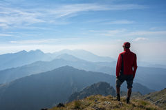 Hiker looking over the mountain ridges. From the top of the mountain Royalty Free Stock Photo